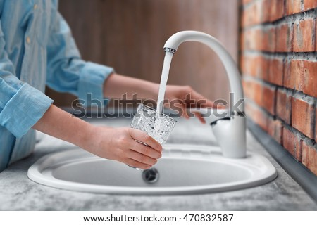 Female hands pouring water in glass cup #470832587
