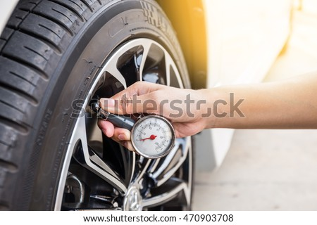 Close-Up Of Hand holding pressure gauge for car tyre pressure measurement #470903708