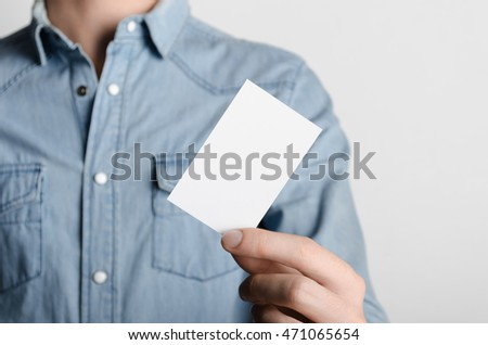 Business Card Mock-Up (85x55mm) - Man in a denim shirt holding a blank card on a gray background.
