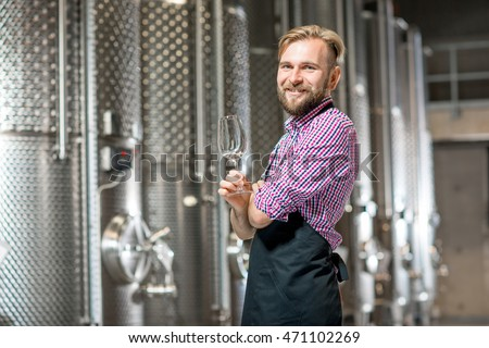 Portrait of a handsome wine maker in working apron with the wine glass at the manufacture with metal tanks for wine fermentation. Wine production at the modern factory #471102269