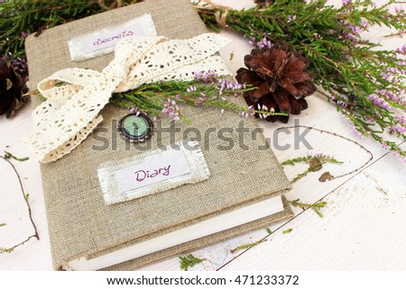 Romantic decorated diary book on white wooden table with natural piny cone and bunch of wild erica / heather. Dreaming concept #471233372