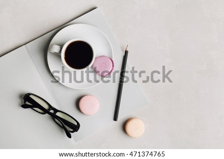 Morning cup of coffee, empty notebook, pencil, glasses and cake macaron on gray desk overhead view. Beautiful breakfast. Flat lay.