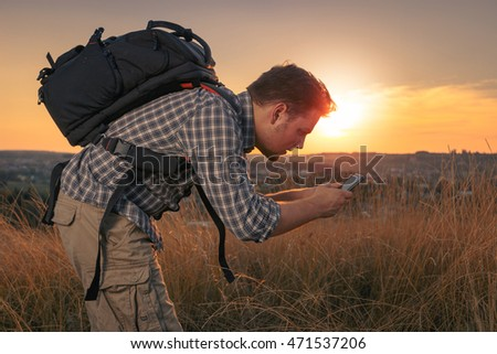 Young guy with a backpack on a trip. Curious hiker photographs. Tourist with a cameraphone, making a photo of interesting insect on a grass.  Smartphone, used as research tool.