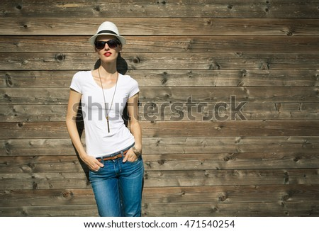 Fashionable woman posing in jeans and white shirt against a wooden background.  #471540254