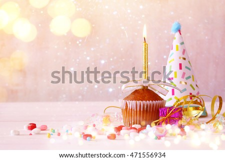 Birthday concept with cupcake and candle, party hat on wooden table. Glitter lights overlay