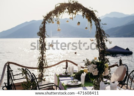 destination wedding arch and banqouet covered table at sunset pierce with sea and mountain view.  Banqu #471608411