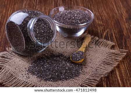 Chia seeds in small jars on wooden background, selective focus #471812498