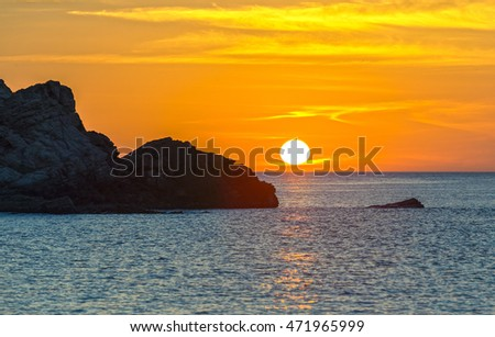 Sunrise over the bay with rocks protruding path toward the sun was jutting out of the water gradually making yellow skies welcomed the new day of peace and beautiful #471965999