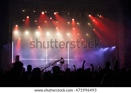 Crowd at concert - Cheering crowd in front of bright colorful stage lights #471996493