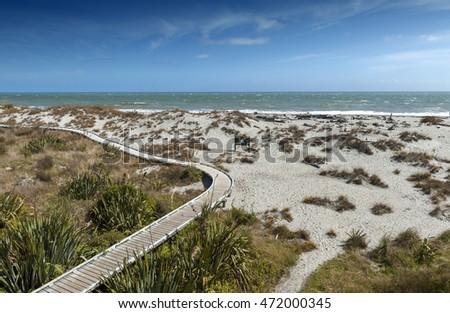 Wooden walkway by the beach at Tauparikaka Marine Reserve, Haast, New Zealand Royalty-Free Stock Photo #472000345