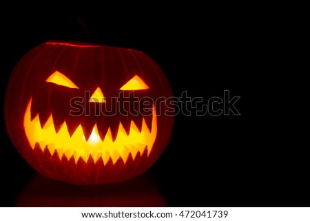 Carved Halloween pumpkin on dark background with copy space #472041739
