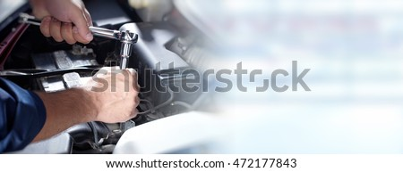 Hands of car mechanic in auto repair service. Royalty-Free Stock Photo #472177843