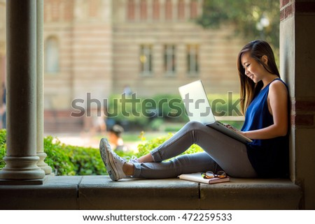 College student studying on campus outdoor with laptop casual lifestyle #472259533