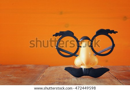 Halloween holiday concept. Funny mustache mask, on wooden table