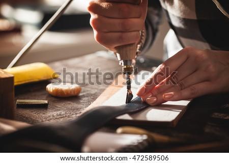 Leather handbag craftsman at work in a workshop #472589506