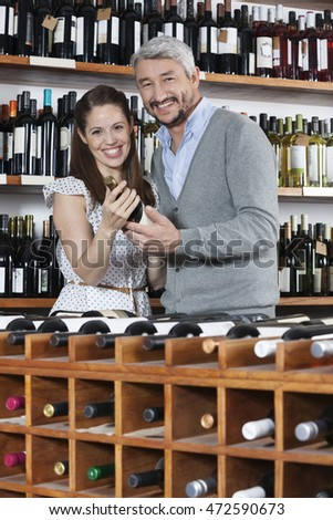 Portrait Of Couple With Wine Bottles Standing At Rack #472590673