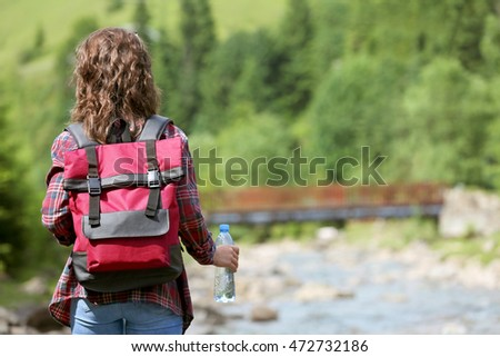 Woman holding bottle with fresh water on beautiful river landscape #472732186
