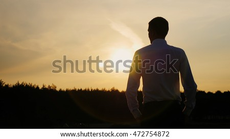 Confident businessman looking forward to the sunset. Well dressed. Concept: hope, dreams, new horizons #472754872