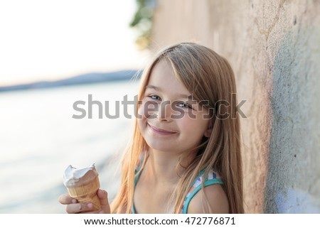 A Beautiful little girl eats ice-cream in the summer #472776871