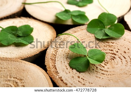 Green four-leaf clovers on wooden background #472778728