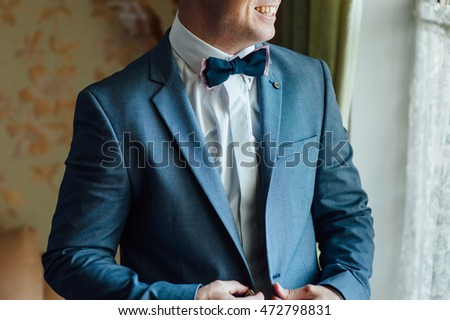 groom clasping stylish watch band on his wrist and bow tie #472798831