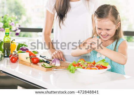 Cute little girl cooking with her mother. Healthy food, cooking healthy salad with vegetables ingredients. Mom and daughter cooking together. Recipe food for baby or child #472848841