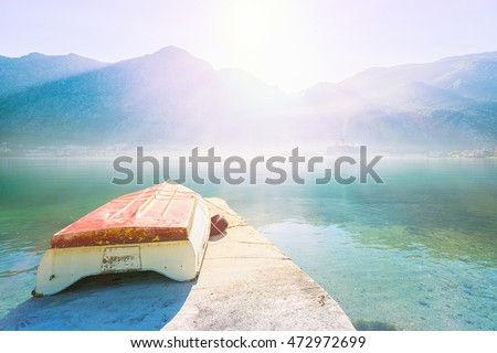 Early misty morning on the pier with old fisshing boat , Kotor city and mountain views. Kotor bay. Montenegro #472972699