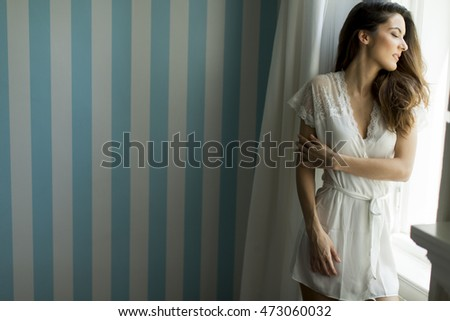 Pretty young woman by the window in the room #473060032