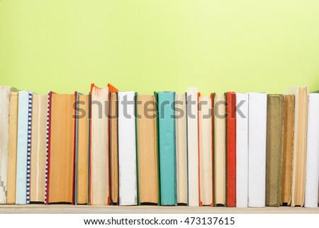 Colorful composition with vintage old hardback books stacking, diary on wooden deck table and green background. Back to school. Copy Space. Education. #473137615