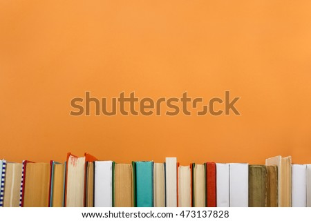 Books on grunge wooden table desk shelf in library. Back to school background with copy space for your ad text. Old hardback no labels, blank spine #473137828