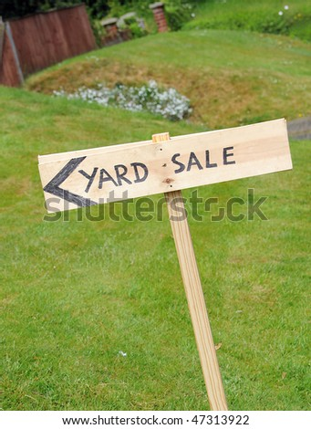 A wooden hand painted yard sale sign outside
