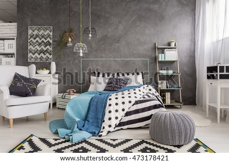 Spacious new design bedroom with carpet, armchair, large bed and decorative wall finish  #473178421