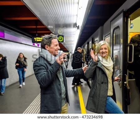 Senior couple standing at the underground platform, entering tra #473234698