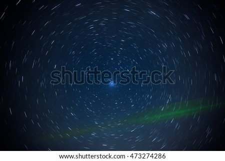 Star trails around polar star with ray of green laser pointer. #473274286