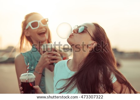 Girls have fun with drinks at the sunset