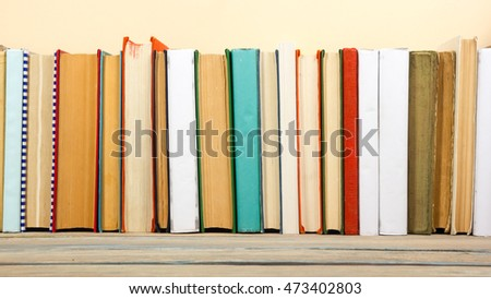 Books on grunge wooden table desk shelf in library. Back to school background with copy space for your ad text. Old hardback   no labels, blank spine #473402803