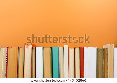 Books on grunge wooden table desk shelf in library. Back to school background with copy space for your ad text. Old hardback no labels, blank spine #473402866