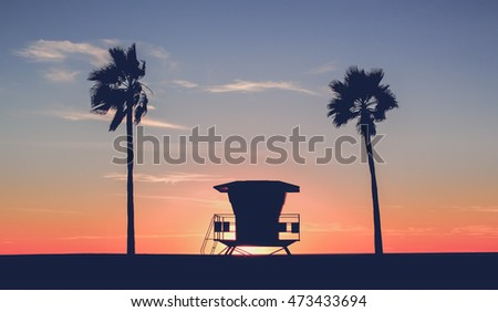 Vintage photo of a silhouette of a  Lifeguard tower on the beach at sunset with palm trees
