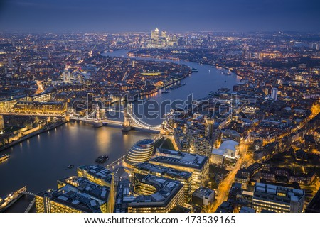 London, England - Aerial Skyline view of London with the iconic Tower Bridge, the Tower of London and skyscrapers of Canary Wharf at blue hour #473539165