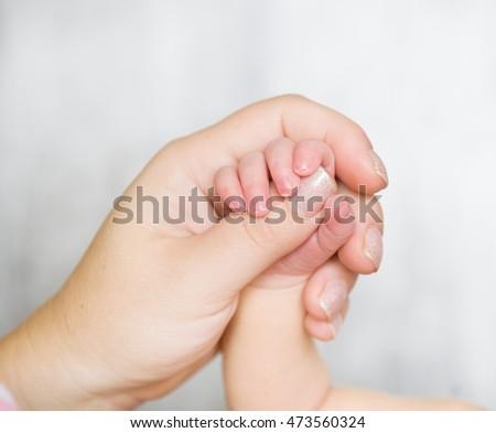 Newborn baby hand in mom's hand #473560324
