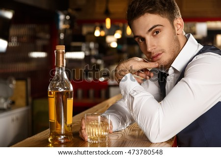 Mind if I join? Shot of an attractive young man looking to the camera seductively sitting at the bar having a glass of whiskey  #473780548