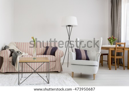 Light interior with upholstered pattern sofa, comfortable armchair, dining table with chairs in the background #473950687
