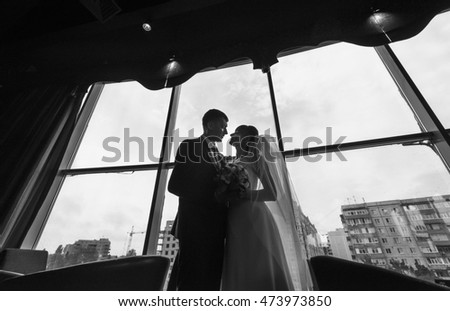 Bride and groom at wedding Day. Wedding photo session in interior. Bridal couple, Happy Newlywed woman and man embracing. Romantic wedding. Black and white. #473973850