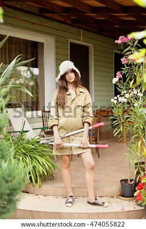 Beautiful girl with long hair gardener in working clothes standing with a large garden scissors in his hand. On her head wearing a straw hat. #474055822