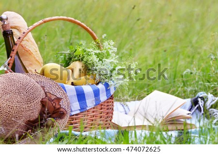 Picnic basket with fruits wine and bread on the grass with book and hat #474072625