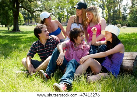 happy group of friends smiling outdoors in a park #47413276