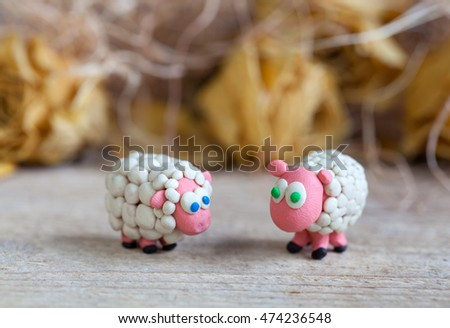 Plasticine world - little homemade white sheep with blue and green eyes stand on a wooden floor, selective focus and place for text