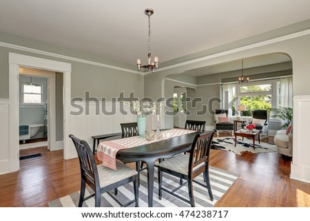 View of a classic dining room with gray walls and medium tone hardwood floors. Dark brown table set on a striped rug. Living room behind. Northwest, USA