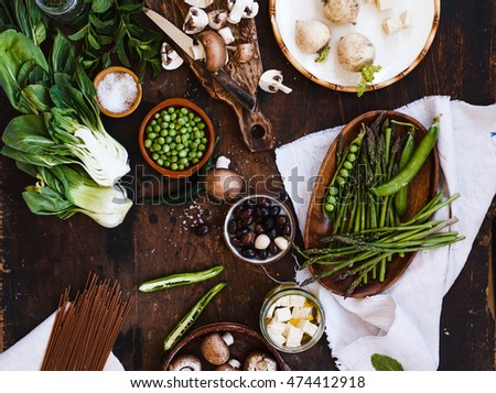 Mix green ingredients. Composition ingredients with mushroom, asparagus, green beans, olive, tofu cheese, bok choy, zucchini and fresh herbs on a dark table. #474412918