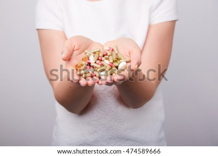 many pills and capsules in women in the hands #474589666